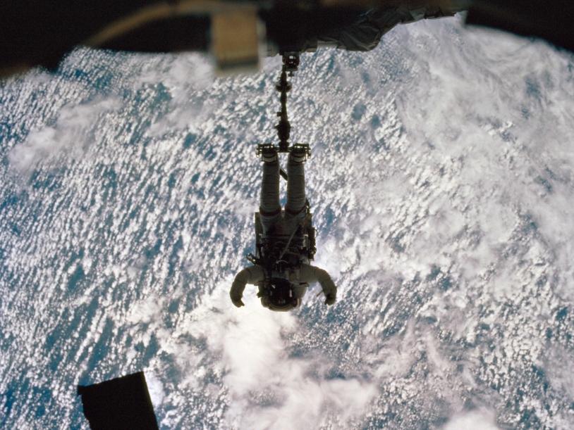 Sortie extravéhiculaire au-dessus de la Terre et ses nuages